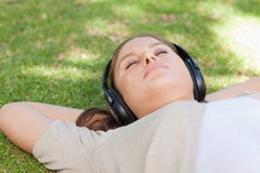 Relaxed woman lying on the lawn enjoying music Stock Images