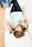 Relaxed woman lying on the sofa holding a card Royalty Free Stock Photography