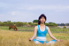 Relaxed woman meditates. Relaxed sports woman meditates outside Stock Image
