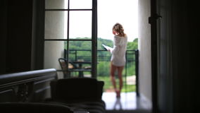 Relaxed woman in the morning reading her book on balkony. View from darkened room stock video footage