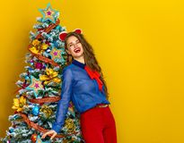 Relaxed woman near Christmas tree isolated on yellow background Royalty Free Stock Photo