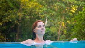 Relaxed woman in open swimming pool. Girl in open swimming pool. Summer vacation vintage toned photo. Tropical jungle hotel scene. Exotic holiday. Outdoor Royalty Free Stock Image