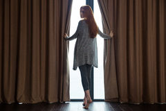 Relaxed  woman opening curtains and looking back Stock Photo