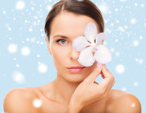 Relaxed woman with orСЃhid flower over eye Royalty Free Stock Image