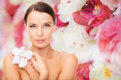 Relaxed woman with orhid flower Stock Images