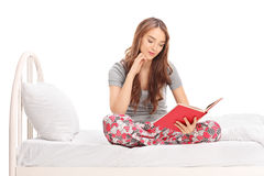 Relaxed woman in pajamas reading a book Stock Images
