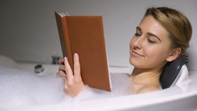 Relaxed woman reading book in bath with foam bubbles, evening at home, close-up stock video