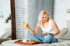 Relaxed woman reading book in bed Royalty Free Stock Photography