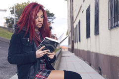 Relaxed woman reading a book sitting in the backyard. Stock Photos