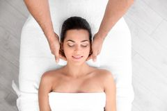 Relaxed woman receiving head massage in wellness center. Top view stock photography