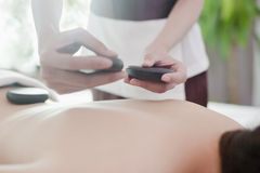 Relaxed Woman Receiving Hot Stone Massage Stock Photo