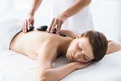Relaxed woman receiving hot stone massage Royalty Free Stock Images