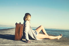 Relaxed woman resting after a long journey with her big suitcase. In front of the sea Stock Images