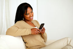 Relaxed woman sending a message by the cellphone Royalty Free Stock Image