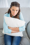 Relaxed woman sitting on sofa holding pillow Royalty Free Stock Photo