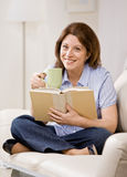 Relaxed woman sitting on sofa reading booK Royalty Free Stock Photos