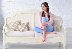 Relaxed woman sitting on a vintage sofa Royalty Free Stock Photo