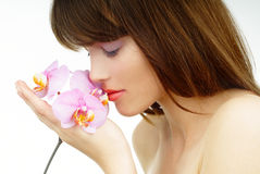 Relaxed woman smelling an orchid stock photos