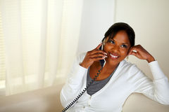 Relaxed woman smiling and conversing on phone Royalty Free Stock Photo