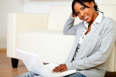 Relaxed woman smiling at you with a laptop Royalty Free Stock Image