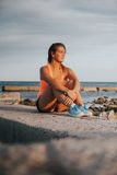 Relaxed woman in sportswear at the seashore. Royalty Free Stock Photography