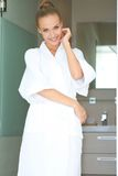 Relaxed woman standing in white bathrobe Stock Photo