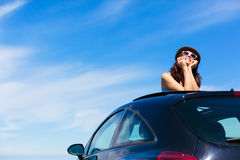 Relaxed woman on summer vacation leaning out sunroof Stock Photography