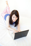 Relaxed woman surfing the internet lying on a bed Stock Image