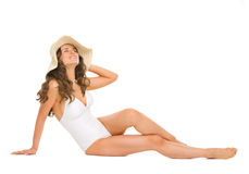 Relaxed woman in swimsuit and hat laying on floor Stock Images