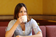 Relaxed woman thinking while is drinking a cup of coffee Stock Photos