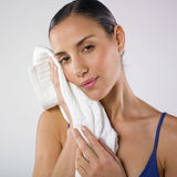 Relaxed woman with towel. A studio portrait of a beautiful young woman leaning her face against a white towel with a relaxed expression on her face Royalty Free Stock Photo