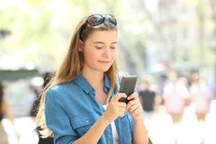 Relaxed woman uses a smart phone in the street. Relaxed woman uses a smart phone walking in the street of a big city Stock Photo