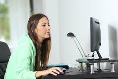Relaxed woman using a desktop computer at home stock photos