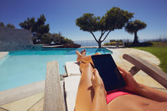 Relaxed woman using digital tablet by poolside. Relaxed woman using digital tablet by the swimming pool. Tanned female model sunbathing and holding tablet PC at Stock Photos