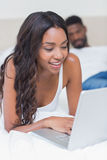 Relaxed woman using laptop on bed Royalty Free Stock Photos