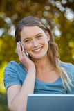 Relaxed woman using laptop and mobile phone at park Stock Images
