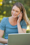 Relaxed woman using laptop and mobile phone at park Royalty Free Stock Images