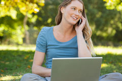 Relaxed woman using laptop and mobile phone at park Stock Photo