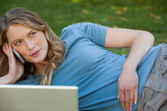 Relaxed woman using laptop and mobile phone at park Stock Image