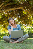 Relaxed woman using laptop and mobile phone at park Royalty Free Stock Photos