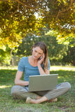 Relaxed woman using laptop and mobile phone at park Royalty Free Stock Image