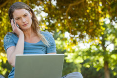 Relaxed woman using laptop and mobile phone at park Stock Photography