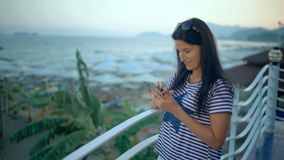 Relaxed woman using a smart phone in a bar or hotel terrace on holidays. Relaxed woman using a smart phone in a bar or hotel terrace on holidays stock footage