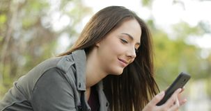 Relaxed woman using a smart phone in a park. Relaxed woman using a smart phone sitting in a park with a green background