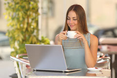 Relaxed woman watching a laptop in a restaurant Stock Images
