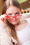 Relaxed woman wearing red glasses sitting on chair Stock Image