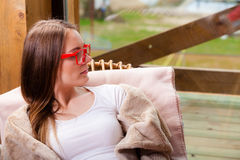 Relaxed woman wearing red glasses sitting on chair Royalty Free Stock Image