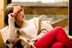 Relaxed woman wearing red glasses sitting on chair Royalty Free Stock Images
