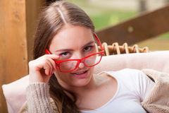 Relaxed woman wearing red glasses sitting on chair Stock Photo