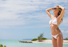 Relaxed woman in white bikini on the beach stock photo